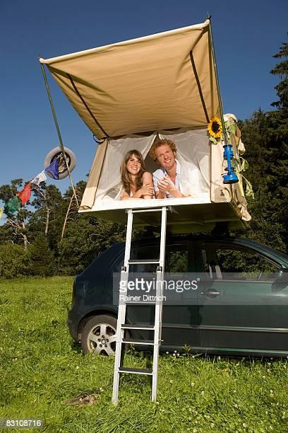 Germany, Bavaria, couple lying inside tent on car, smiling