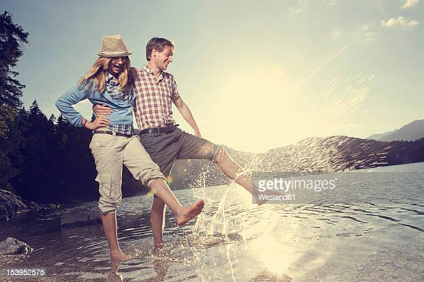 Germany, Bavaria, Couple playing in water, smiling