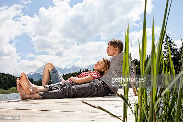 Germany, Bavaria, Couple relaxing on jetty