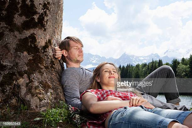 Germany, Bavaria, Couple relaxing under tree