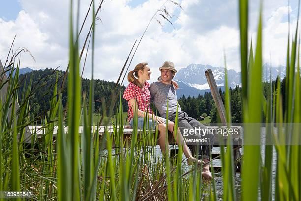 Germany, Bavaria, Couple sitting on jetty, smiling