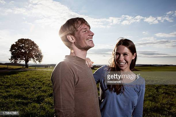 Germany, Bavaria, Couple standing in field, smiling