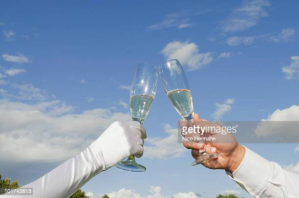 Germany, Bavaria, Couple toasting with champagne glasses, close-up of hands