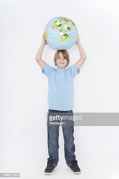 Germany, Bavaria, Ebenhausen, Boy holding earth globe against white background, smiling, portrait
