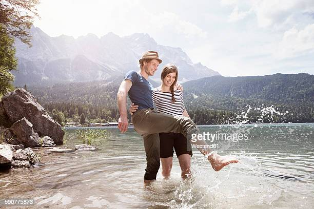 Germany, Bavaria, Eibsee, happy couple splashing in water