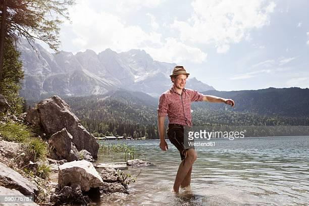 Germany, Bavaria, Eibsee, happy man in lederhosen wading in water