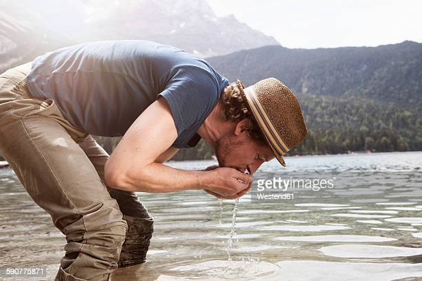 Germany, Bavaria, Eibsee, man drinking water from lake