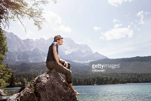 Germany, Bavaria, Eibsee, man sitting on rock on lakeshore