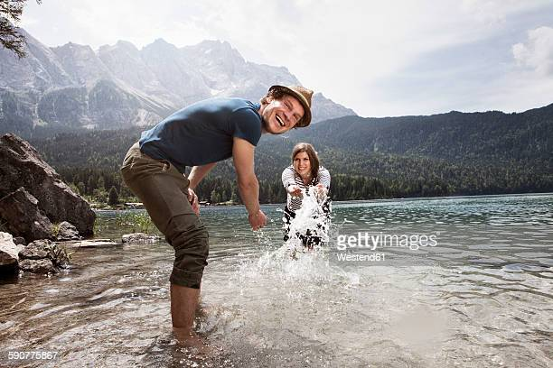 Germany, Bavaria, Eibsee, playful couple splashing in water