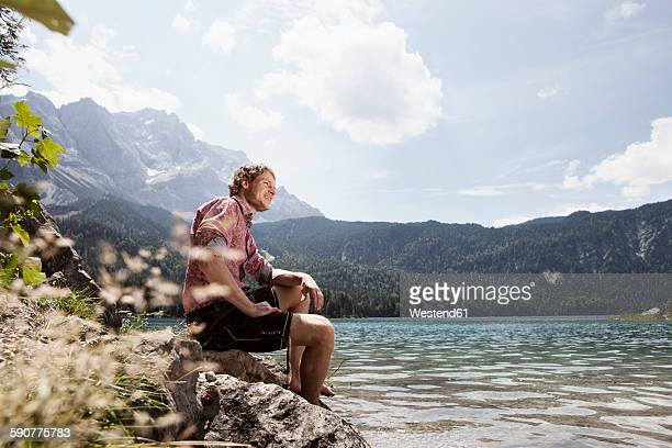 Germany, Bavaria, Eibsee, smiling man in lederhosen sitting on lakeshore
