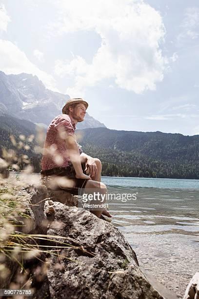 Germany, Bavaria, Eibsee, smiling man in lederhosen sitting on lakeshore