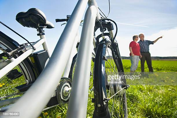 Germany, Bavaria, Electric bicycle, Senior man pointing in background