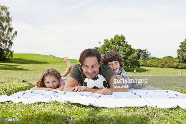 germany, bavaria, family lying on blanket in park, smiling, portrait - lying on front stock pictures, royalty-free photos & images