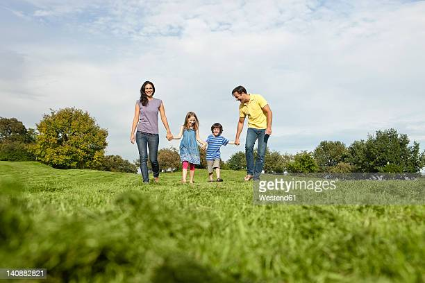 Germany, Bavaria, Family walking in grass at park