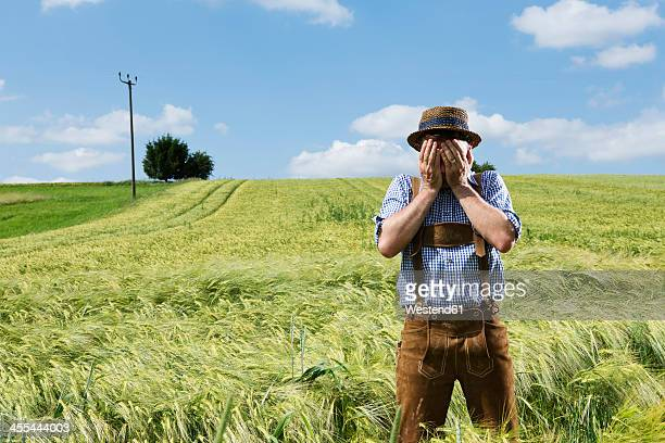 Germany, Bavaria, Farmer covering his face in field