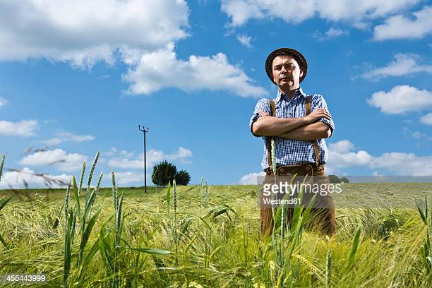 Germany, Bavaria, Farmer standing with arms crossed in field