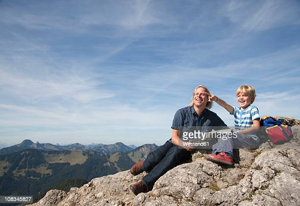 Germany, Bavaria, Father and son (4-5 Years) looking away with map on mountain summit
