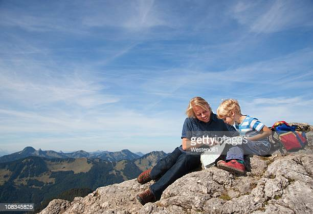 Germany, Bavaria, Father and son (4-5 Years) looking into map at mountain summit