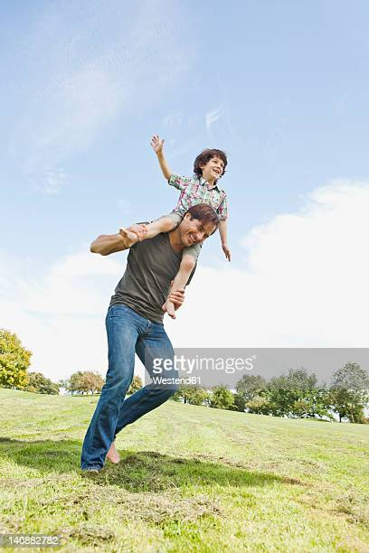 germany, bavaria, father carrying son on shoulder in park, smiling - carrying a person on shoulders stock photos and pictures