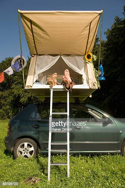 Germany, Bavaria, couple lying in tent on car top, low section