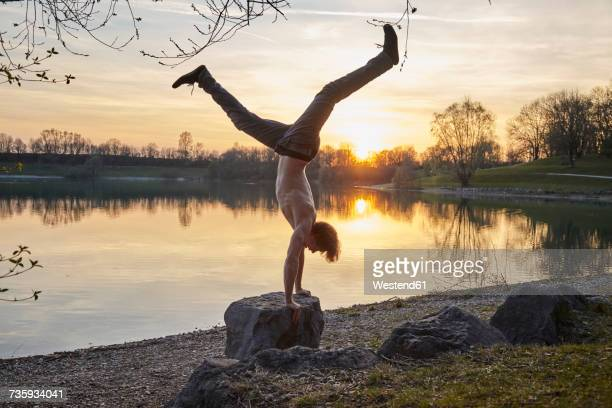 Germany, Bavaria, Feldkirchen, man doing a handstand at lakeshore