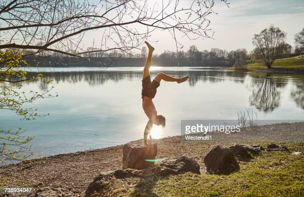 germany, bavaria, feldkirchen, man doing a handstand at lakeshore - leichter stock-fotos und bilder