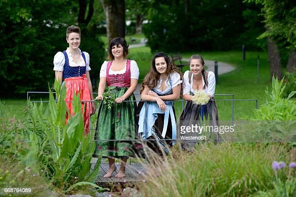 germany, bavaria, four smiling women wearing dirndls - roupa tradicional - fotografias e filmes do acervo