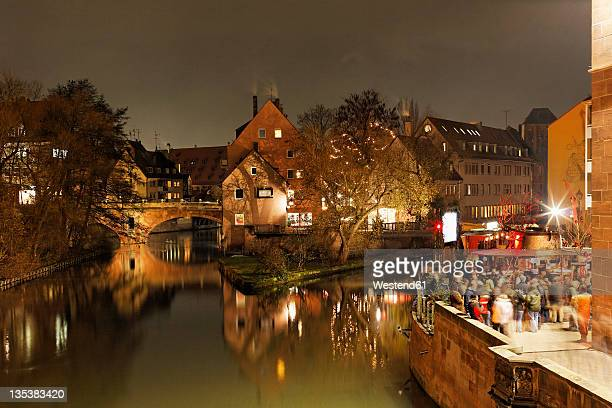 Germany, Bavaria, Franconia, Nuremberg, View of christmassy stall besides river