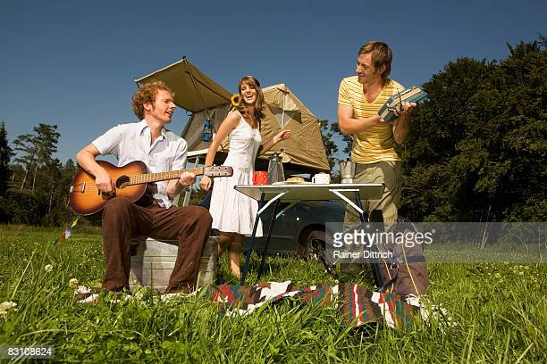 Germany, Bavaria, three friends playing music and dancing in meadow