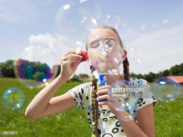 Germany, Bavaria,  girl (10-11) blowing soap bubbles