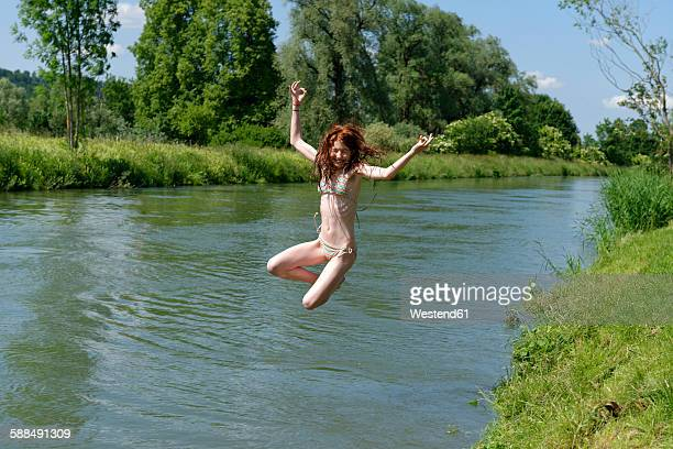 germany, bavaria, girl jumping into river loisach - redhead girl stock photos and pictures