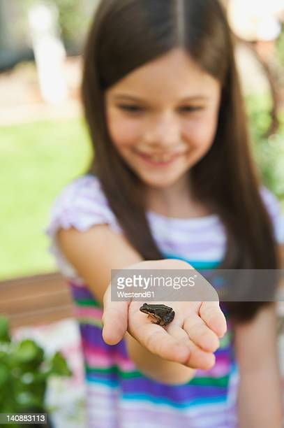 Germany, Bavaria, Girl looking at little frog