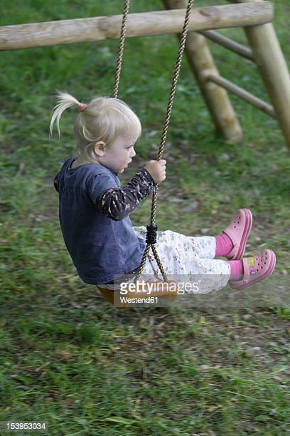 Germany, Bavaria, Girl playing on swing
