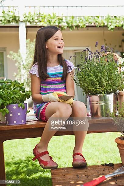 Germany, Bavaria, Girl sitting on garden bench, smiling