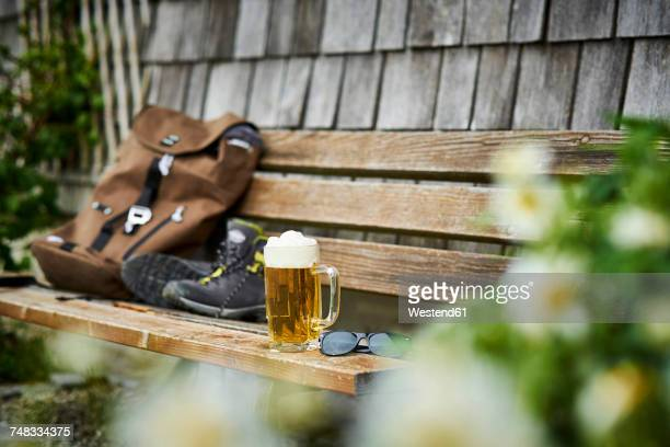 germany, bavaria, glass of beer, backpack, sunglasses and hiking shoes on wooden bench - upper bavaria stock photos and pictures