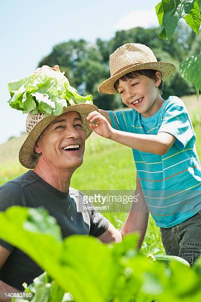 Germany, Bavaria, Grandfather with grandson in vegetable garden, smiling