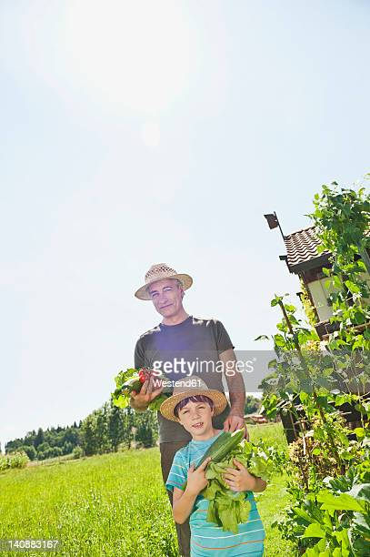 Germany, Bavaria, Grandfather with grandson in vegetable garden, smiling, portrait