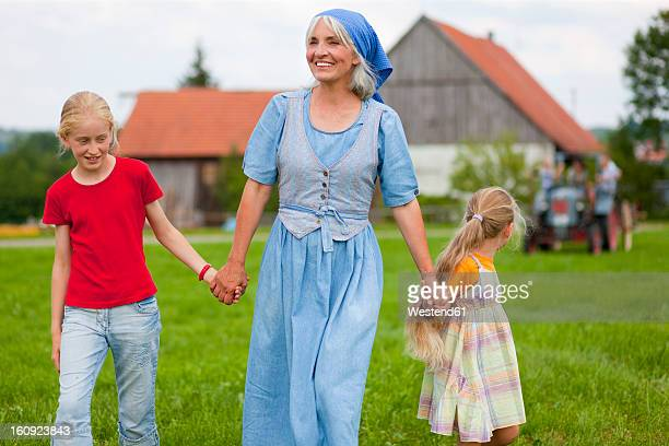 Germany, Bavaria, Grandmother with children walking in front of farmhouse