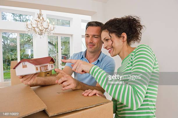 Germany, Bavaria, Grobenzell, Couple standing near cardboard boxes with model house, smiling