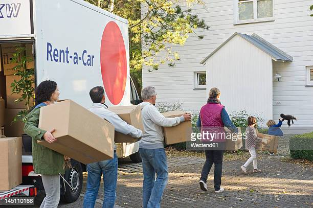 Germany, Bavaria, Grobenzell, Family carrying cardboard box for moving house