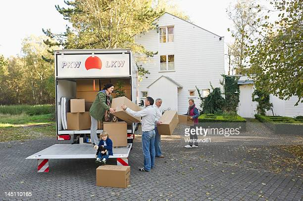 Germany, Bavaria, Grobenzell, Family loading boxes into truck for moving house