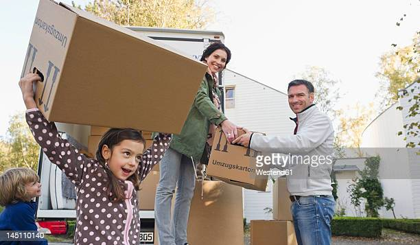Germany, Bavaria, Grobenzell, Family with cardboard boxes for moving house, smiling