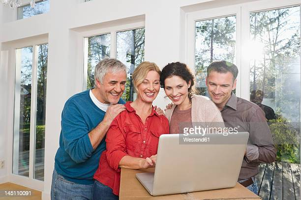 Germany, Bavaria, Grobenzell, Man and woman using laptop, smiling