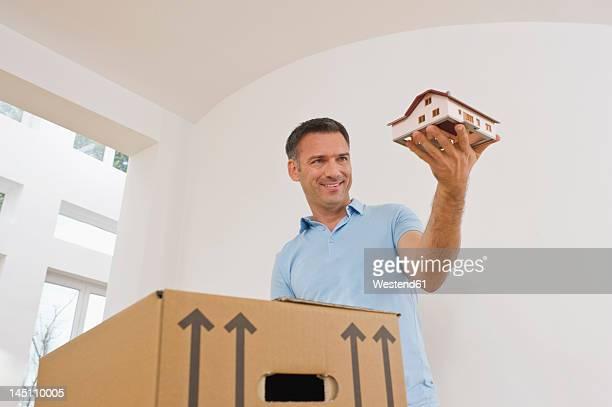 Germany, Bavaria, Grobenzell, Mature man holding model house near cardboard box, smiling