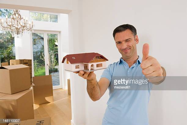 Germany, Bavaria, Grobenzell, Mature man holding model house near cardboard box, smiling, portrait