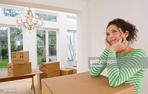 germany, bavaria, grobenzell, mid adult woman standing near cardboard boxes in house, smiling - frauen über 30 stock-fotos und bilder