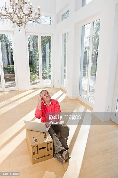 Germany, Bavaria, Grobenzell, Senior man using laptop on cardboard box