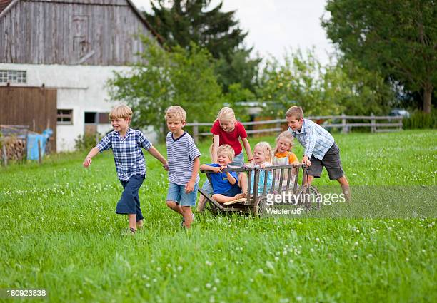 Germany, Bavaria, Group of children playing with hand cart in front of farmhouse
