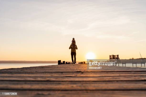 germany, bavaria, herrsching, father carrying daughter on shoulders on jetty at sunset - portare a cavalluccio foto e immagini stock