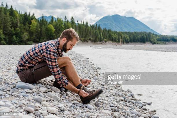 germany, bavaria, hiker sitting at riverside tying his shoe - hiking boots stock photos and pictures